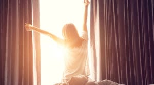 woman opening curtains letting in sunshine